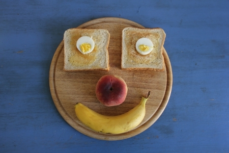 Frühstück-Gesicht mit Ei und Toas