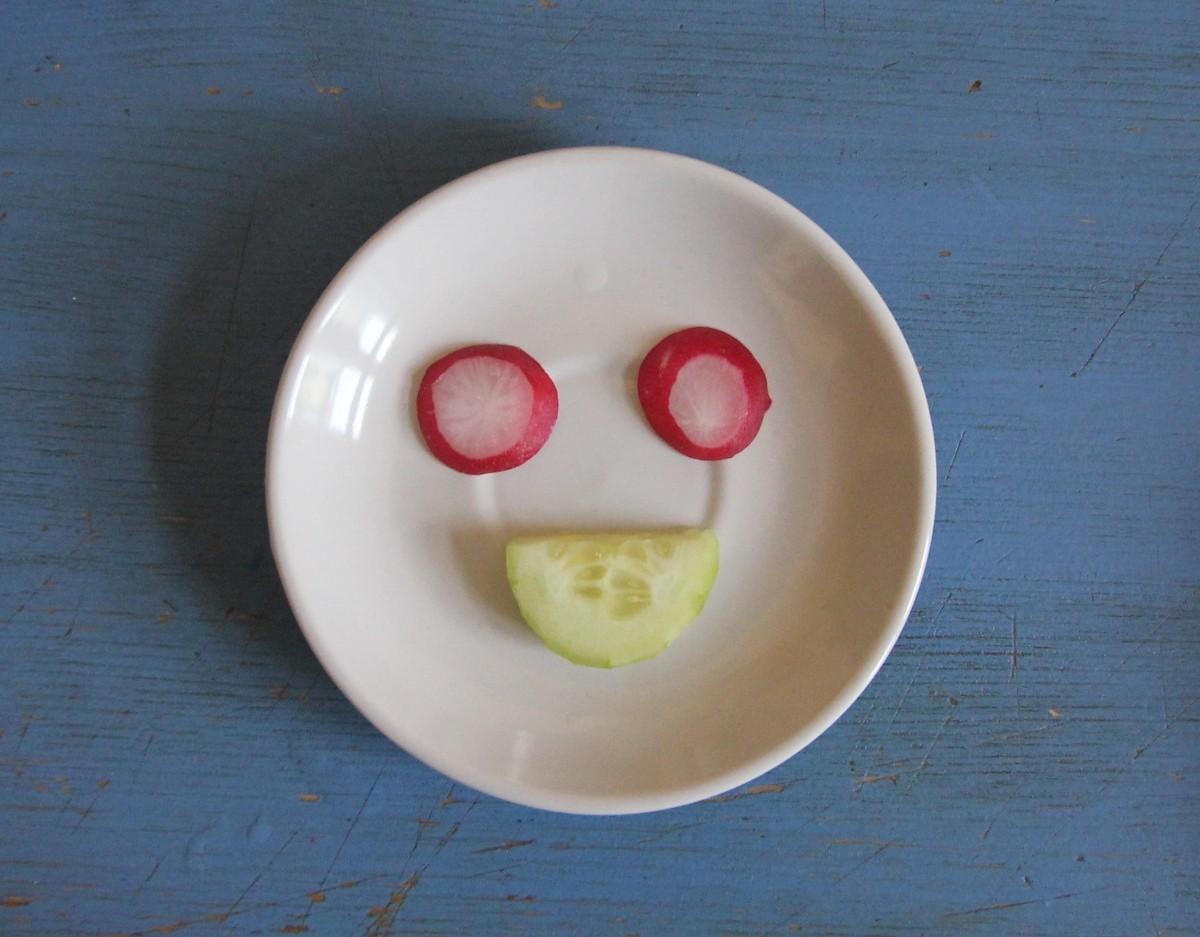 Salatgesicht mit Gurke und Radieschen